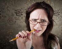 Mulher nervosa que mastiga em um lápis Fotografia de Stock Royalty Free