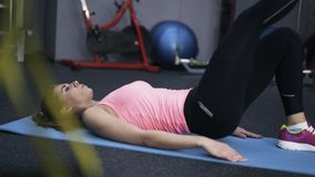 A mulher no Abs fazendo cor-de-rosa exercita em um gym vídeos de arquivo