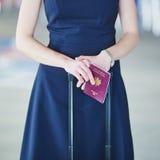 Mulher no aeroporto internacional que guarda o passaporte francês em suas mãos imagem de stock