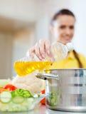A mulher no amarelo derrama o óleo na caçarola fotografia de stock