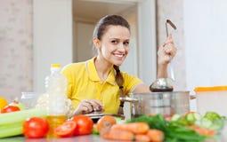 A mulher no amarelo testa o alimento foto de stock royalty free