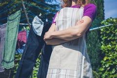 Mulher no avental que está pela linha de roupa Foto de Stock Royalty Free
