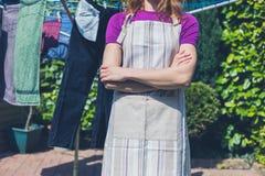Mulher no avental que está pela linha de roupa Fotografia de Stock