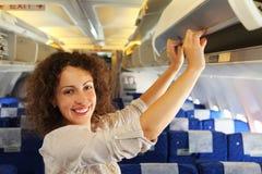 A mulher no avião adiciona a bagagem imagem de stock
