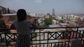 Mulher no balcão com ideia da parte velha Tbilisi, Geórgia, telhados das construções, arranha-céus de vidro filme