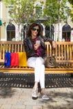 Mulher no banco com sacos de compras que olha o vertical móvel Fotografia de Stock
