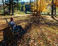 Mulher no banco no parque ensolarado da montanha Carpathian do outono no rio imagem de stock royalty free