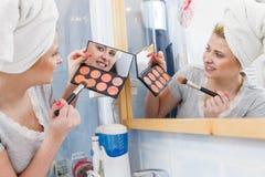 Mulher no banheiro que aplica o bronzer do contorno na escova imagem de stock