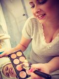 Mulher no banheiro que aplica o bronzer do contorno na escova fotos de stock royalty free