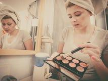 Mulher no banheiro que aplica o bronzer do contorno na escova imagem de stock royalty free