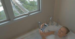 Mulher no banho que toma o selfie com telefone esperto video estoque