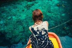 Mulher no barco que olha a água azul clara Imagens de Stock Royalty Free
