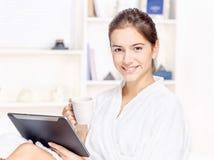 Mulher no bathrobe que relaxa em casa Fotos de Stock Royalty Free
