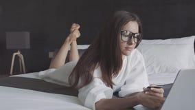 Mulher no bilhete branco do bue do roupão e dos vidros com cartão de crédito e no portátil, mentira na cama Compra em linha video estoque