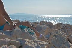 Mulher no biquini que senta-se no litoral e que bronzea-se seus peitos e céu azul imagem de stock