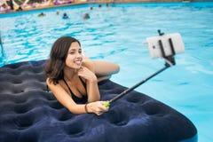 Mulher no biquini que sorri e que toma a foto do selfie no telefone com vara do selfie em um colchão na associação no recurso imagens de stock royalty free