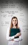 A mulher no branco está guardando um dobrador Equação foto de stock