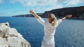 Mulher no branco na frente do mar azul que aumenta os braços que aprecia a liberdade durante o curso das férias das férias de ver vídeos de arquivo
