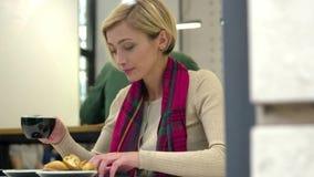 Mulher no café do café e no telefone celular bebendo da utilização vídeos de arquivo