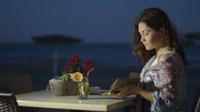 Mulher no café que toma o caderno fora da bolsa, fazendo anotações no diário, inspiração vídeos de arquivo