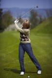 Mulher no campo de golfe que prepara-se para um balanço Fotos de Stock