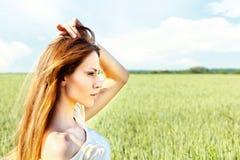 Mulher no campo de trigo no dia ensolarado Imagem de Stock