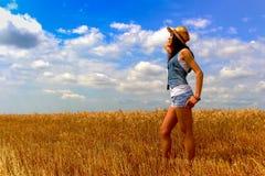 Mulher no campo do centeio no céu nebuloso azul Foto de Stock