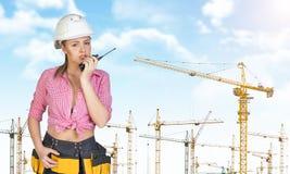 A mulher no capacete de segurança e a ferramenta cercam a fala no walkie imagem de stock royalty free