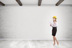 Mulher no capacete de segurança na sala vazia Imagem de Stock