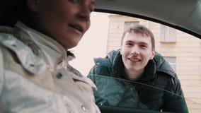 A mulher no carro abre a janela assim que a parte externa do homem pode falar ao passageiro video estoque