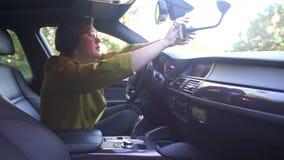 A mulher no carro ajusta o telefone no suporte vídeos de arquivo