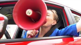 A mulher no carro vermelho está sentando-se É nervosa A menina toma o orador e a conversa nela Igualmente usa chifres de carro vídeos de arquivo