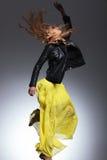 Mulher no casaco de cabedal e no vestido amarelo que fazem um salto Fotografia de Stock Royalty Free