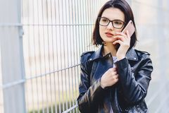Mulher no casaco de cabedal nos vidros que fala no telefone imagens de stock