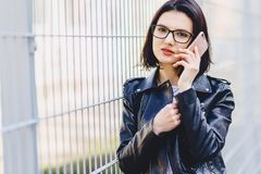 Mulher no casaco de cabedal nos vidros que fala no telefone imagem de stock