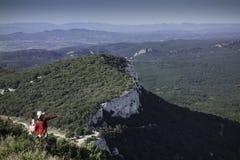 Mulher no casaco vermelho que aponta à vista no ramalhete do mont fotografia de stock