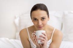 Mulher no chá bebendo da cama Imagem de Stock