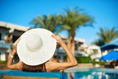 Mulher no chapéu branco grande que encontra-se em um vadio perto da piscina no hotel, horas de verão do conceito viajar imagens de stock royalty free