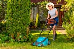 Mulher no chapéu com o cortador de grama bonde no fundo do jardim Imagem de Stock