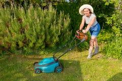 Mulher no chapéu com o cortador de grama bonde no fundo do jardim Imagens de Stock