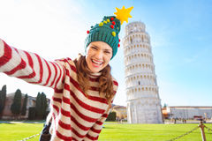 Mulher no chapéu da árvore de Natal que toma o selfie em Pisa imagem de stock