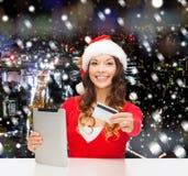 Mulher no chapéu de Santa com PC da tabuleta e cartão de crédito Imagens de Stock
