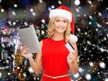 Mulher no chapéu de Santa com PC da tabuleta e cartão de crédito Fotografia de Stock Royalty Free