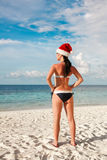 Mulher no chapéu de Santa na praia Fotografia de Stock