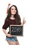 Mulher no chapéu de Santa que guarda o cartão com palavra de 2016 Imagens de Stock Royalty Free