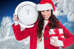 Mulher no chapéu de Santa que guardam o presente e em um pulso de disparo de parede que mostra poucos minutos à meia-noite Fotos de Stock Royalty Free