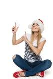 Mulher no chapéu de Santa que senta-se no assoalho que aponta e que olha acima Imagem de Stock