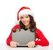 Mulher no chapéu do ajudante de Santa com computador portátil Fotos de Stock