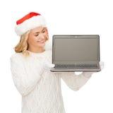 Mulher no chapéu do ajudante de Santa com computador portátil Imagem de Stock