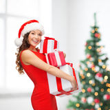 Mulher no chapéu do ajudante de Santa com muitas caixas de presente Foto de Stock
